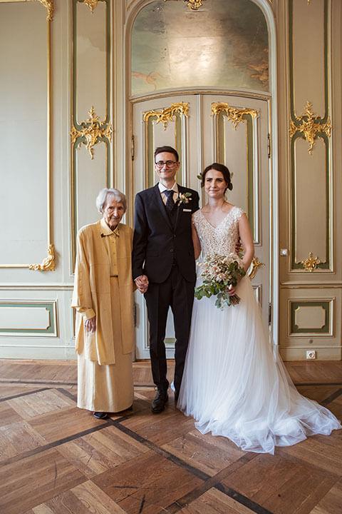 Familienfoto auf Hochzeit vom Brautpaar mit der Oma des Bräutigams