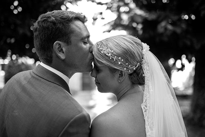 romantisches hochzeitsbild von einem Kuss in schwarz weiss